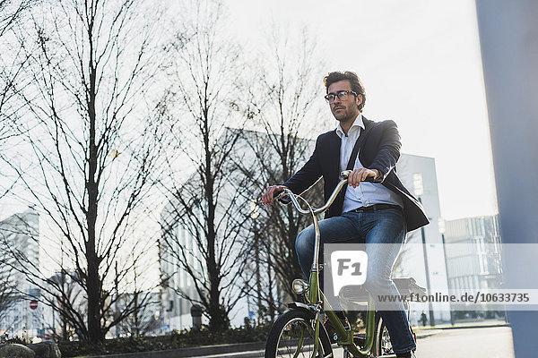 Deutschland  Frankfurt  Jungunternehmer in der Stadt Fahrrad fahren
