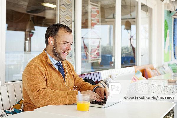 Spanien  Barcelona  lächelnder Geschäftsmann  der am Meer sitzt und einen Laptop benutzt.
