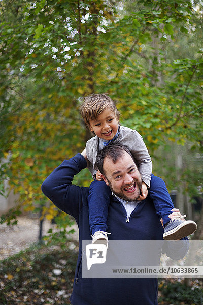 Laughing little boy sitting on his father's shoulders