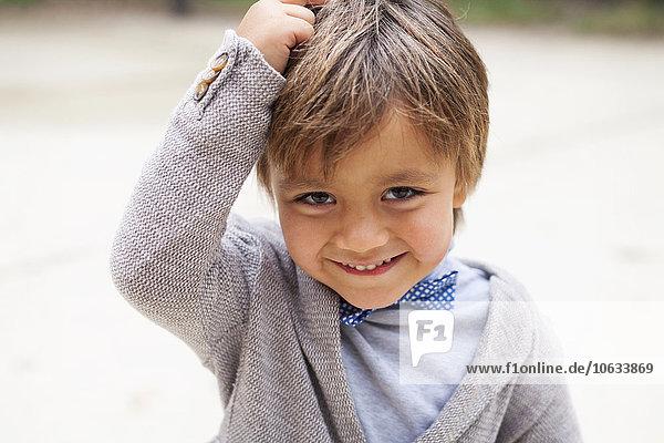 Porträt des lächelnden kleinen Jungen mit der Hand auf dem Kopf Porträt des lächelnden kleinen Jungen mit der Hand auf dem Kopf