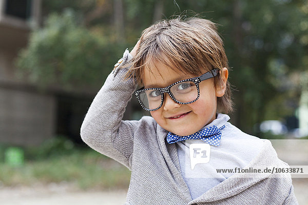 Portrait of smiling little boy with hand on his head wearing bow tie and oversized spectacles