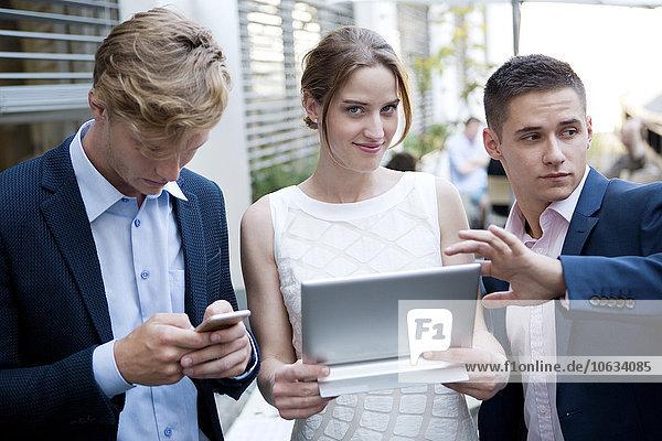Drei junge Geschäftsleute mit digitalem Tablett und Handy im Freien