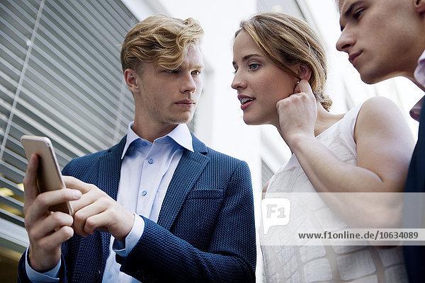 Drei junge Geschäftsleute auf dem Handy