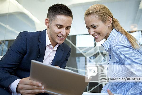 Lächelnder Geschäftsmann und Geschäftsfrau beim Betrachten des digitalen Tabletts im Büro