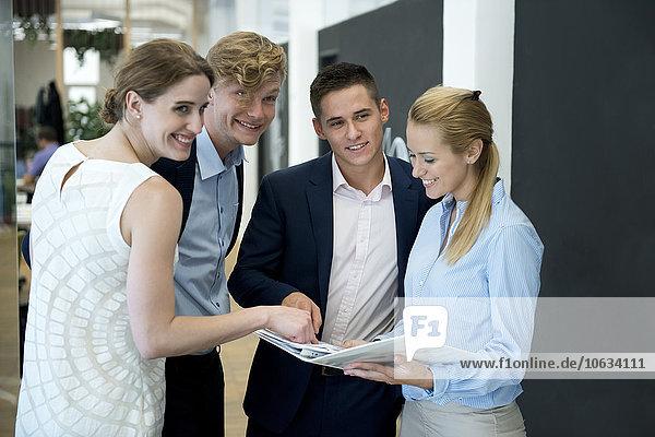 Lächelndes Geschäftsteam im Büro mit Blick auf die Mappe