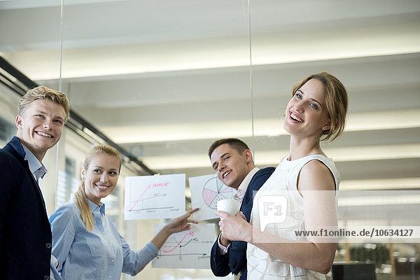 Smiing Business-Team im Büro zeigt auf Chart