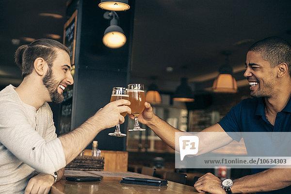 Zwei glückliche Männer in einer Bar  die mit Biergläsern klirren.