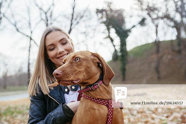 Portrait eines Hundes mit Hundegeschirr mit Besitzer im Hintergrund