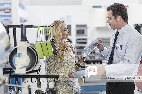 Verkäufer im Gespräch mit dem Kunden beim Einkauf von Küchenutensilien