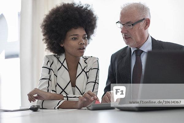 Geschäftsmann und Frau mit Laptop und Taschenrechner
