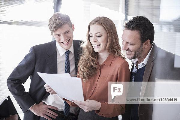 Drei glückliche Kollegen im Büro beim Blick auf die Papiere