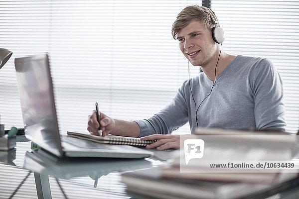 Mann am Schreibtisch mit Kopfhörer