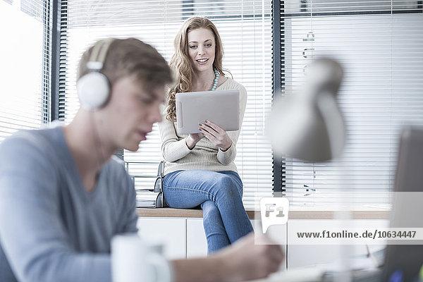 Zwei Kreativprofis mit Kopfhörer und digitalem Tablett im Büro