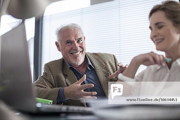 Zwei lächelnde Kollegen im Büro mit Laptop
