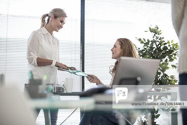 Zwei Kollegen im Büro tauschen Papiere aus