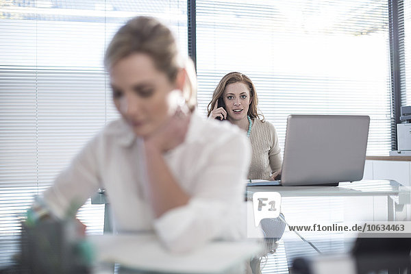 Frau im Büro mit Laptop am Telefon