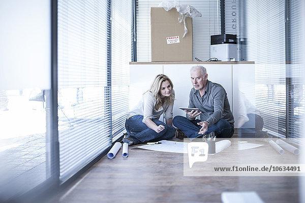 Zwei Kollegen im Bürogeschoss mit digitalem Tablett und Bauplan