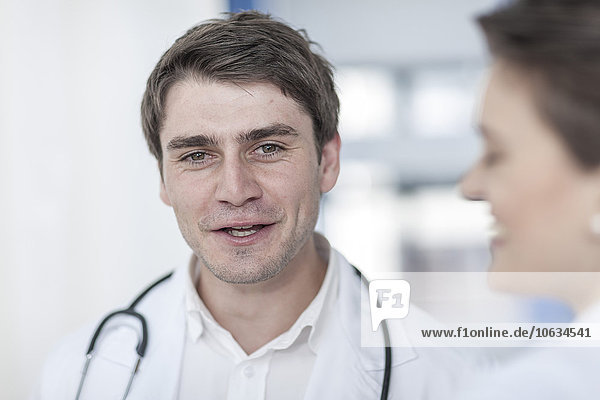 Smiling doctor talking to woman in hospital