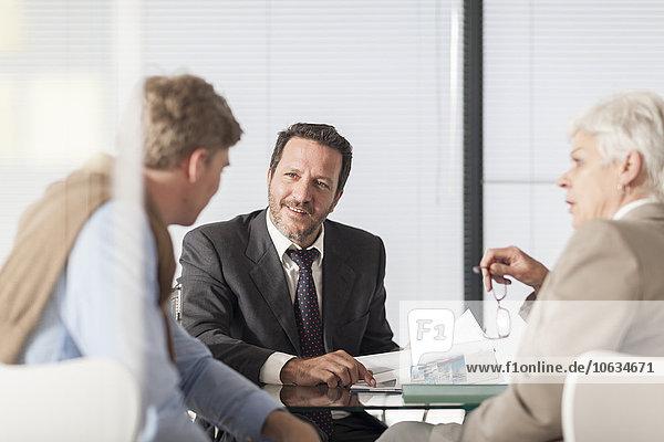 Drei Geschäftsleute diskutieren im Amt