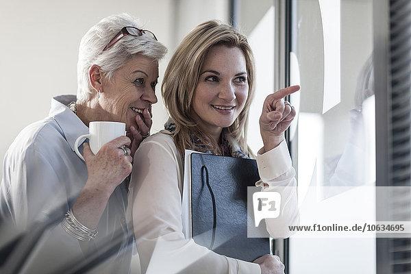 Zwei Frauen im Büro  die durch die Jalousien schauen.
