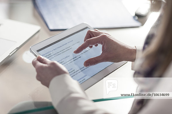 Close-up of person at desk using digital tablet