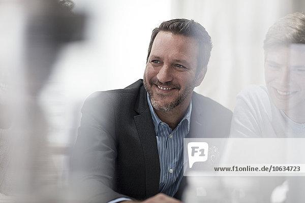 Lächelnder Geschäftsmann im Büro mit Blick auf Kollegen
