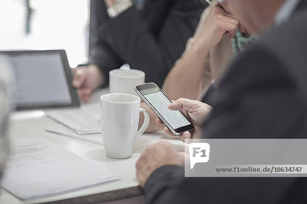 Geschäftsmann mit Handy während der Besprechung