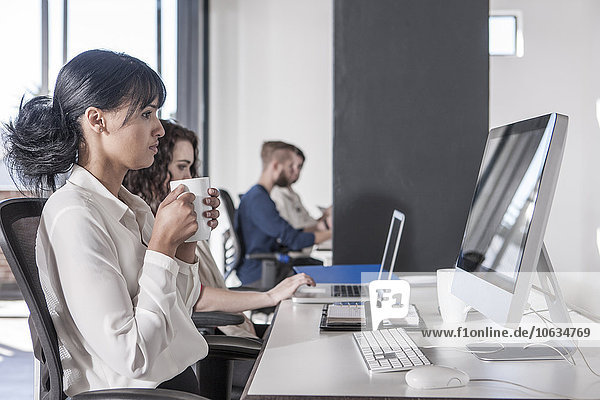 Kreative Profis arbeiten zusammen im Büro  Frau hält eine Tasse Kaffee in der Hand