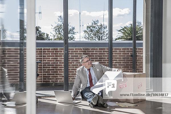 Geschäftsmann auf dem Boden sitzend in einem neuen Büro