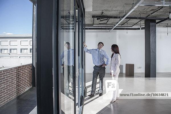 Geschäftsleute stehen am Fenster in neuem offenen Büro