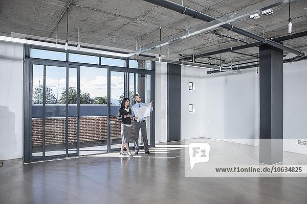 Gewerbetreibende betrachten Bauplan in neuem Großraumbüro