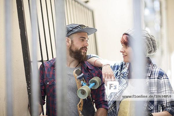 Junge Frau und Mann mit Skateboard im Gespräch