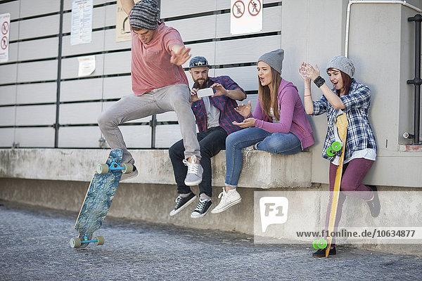 Junger Mann mit Freunden beim Skateboard-Trick