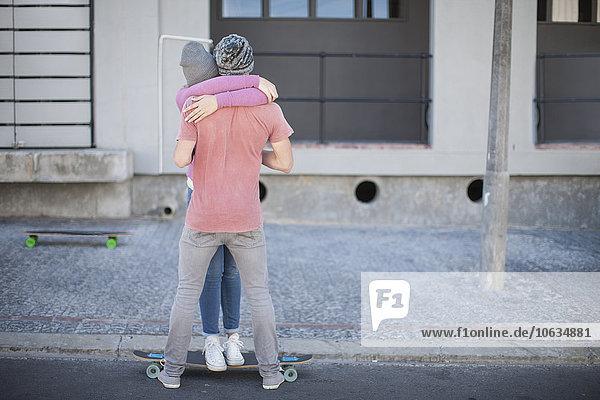 Junges Paar mit Skateboardumarmung auf der Straße