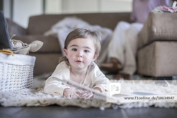 Kleines Mädchen zu Hause auf dem Boden liegend mit Buch