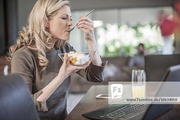 Frau isst Obstsalat und arbeitet zu Hause am Laptop