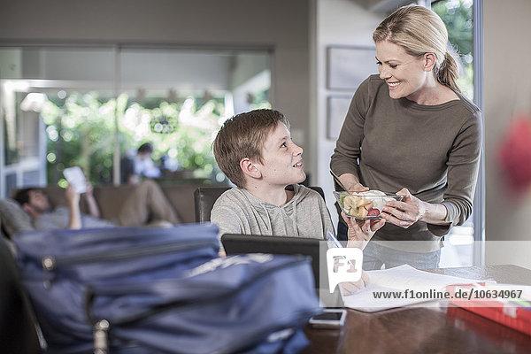 Mutter übergibt Obstsalat an Sohn bei den Hausaufgaben