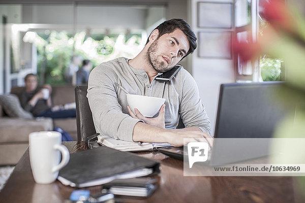 Mann sitzt am Esstisch und arbeitet zu Hause.