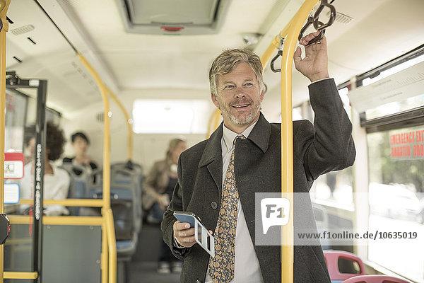 Erwachsener Mann nimmt Stadtbus  hält Smartphone