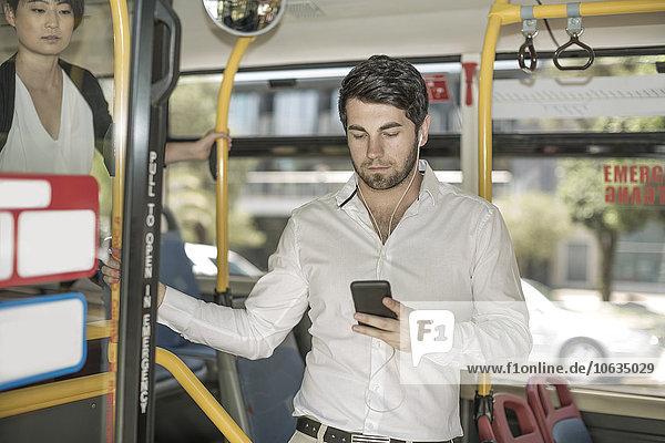 Junger Mann im Stadtbus hört Musik vom Smartphone