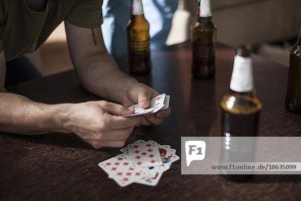 Junger Mann mit Spielkarten auf dem Tisch mit Bierflaschen
