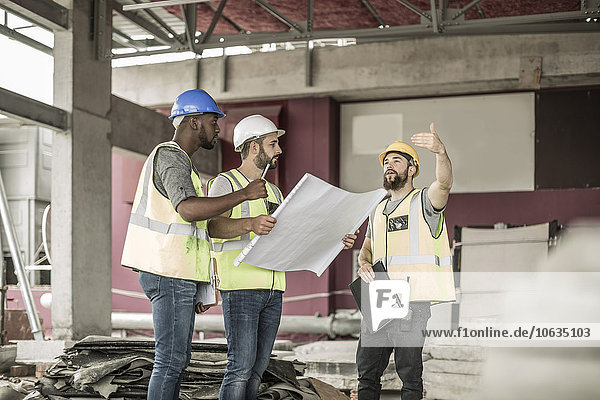 Construction workers discussing building plan in construction site