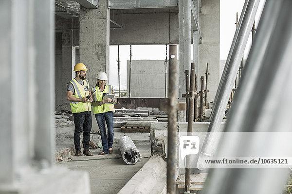 Frau in Arbeitsschutzkleidung und Bauarbeiterin auf der Baustelle