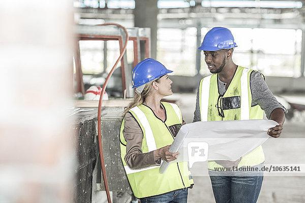 Frau und Bauarbeiter besprechen Bauplan auf der Baustelle