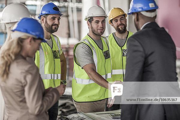 Bauarbeiter und Führungskraft beim Händeschütteln auf der Baustelle