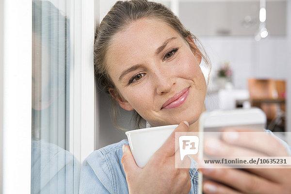 Junge Frau sitzt am Fenster  trinkt Kaffee und liest SMS