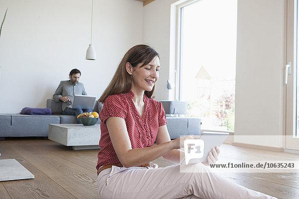 Reife Frau mit digitalem Tablett auf dem Boden im Wohnzimmer  Mann mit digitalem Tablett im Hintergrund
