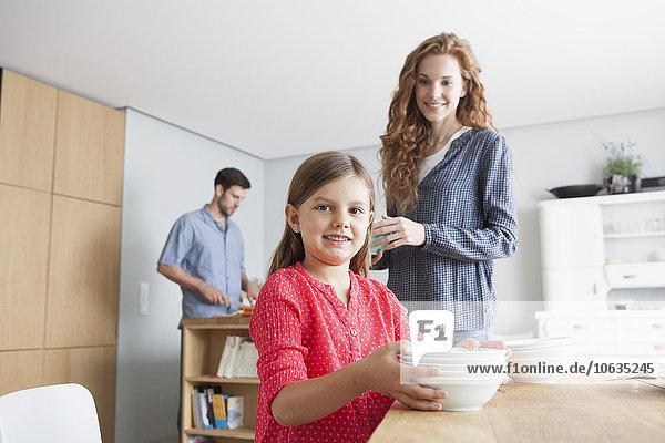 Porträt eines kleinen Mädchens  das den Tisch in der Küche mit seinen Eltern im Hintergrund deckt.