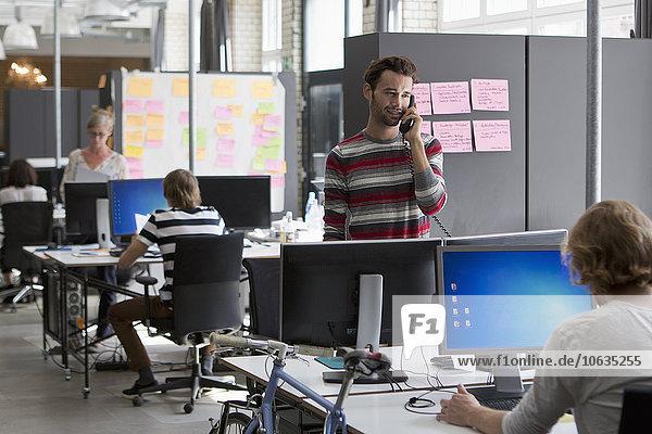 Kollegen  die im Büro arbeiten  Mann  der auf dem Festnetz telefoniert.