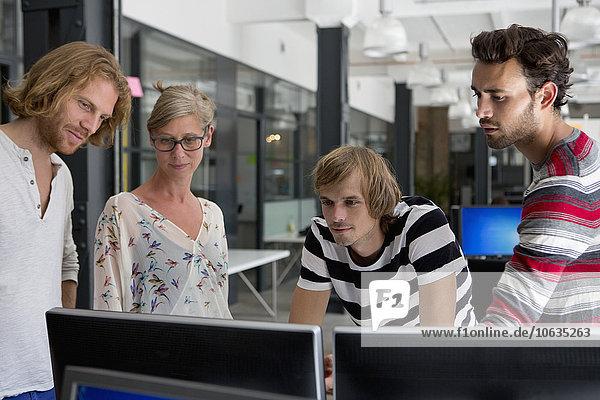 Bürokollegen beim Blick auf den Computer im Büro